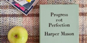 Book showing title progress not perfection next to apple